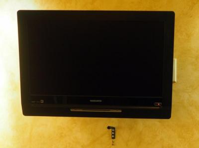 "Magnavox 25"" Wall Mounted Television With Remote, Includes Wall Mount, Bidder Responsible For Proper Removal"