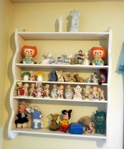 "Ceramic Collectibles Including Raggedy Ann And Andy Planters, Handpainted Bells, Kitty Cats; And Wall Shelf, 34"" x 28"" x 6"""