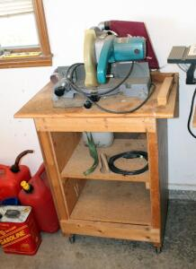 "Makita 10"" Miter Saw Model LS1000 (13"" x 21"" x 21"") With Rolling Wood Stand (35"" x 28.5"" x 21""), Mounted To Stand, Powers On"