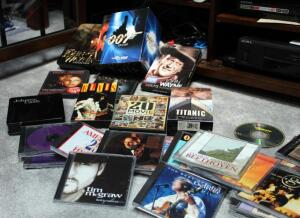 Movie And And CD Assortment, Including John Wayne DVD Set In Box, James Bond DVD Set, VHS Movies, Johnny Cash CD Set And More, Contents Of Shelf