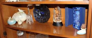 Gallery Originals Lead Crystal Bethlehem Sculpture With Lighted Base, Crystal Dolphin Sculpture, Carnival Glass Plate, Porcelain Eggs, And More, Contents Of Shelf