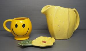 "McCoy Pottery Yellow Pitcher 6"" H, Smiley Face Mug 4"" H And Unmarked Floral Spoon Rest 6"" L"